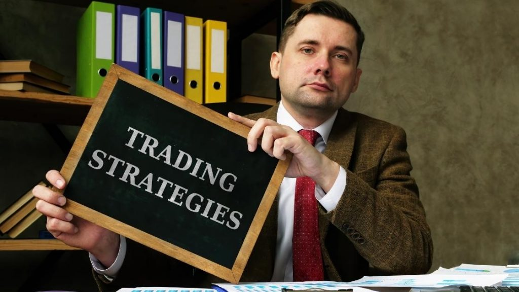 man holding trading strategies sign